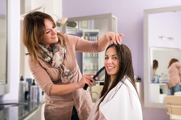 Cabeleireiro, penteando o cabelo de uma jovem mulher