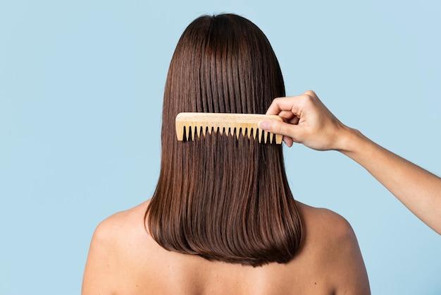 Cabeleireiro penteando o cabelo de uma mulher