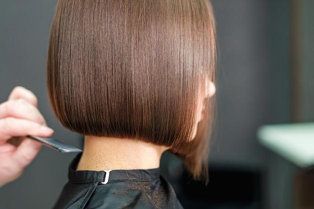 Cabeleireiro penteia cabelo curto morena.