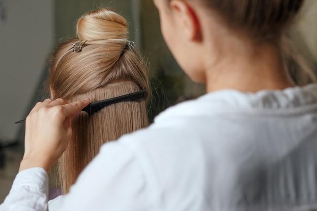 Cabeleireiro penteia o cabelo longo e saudável da cliente após morrer em um salão de beleza