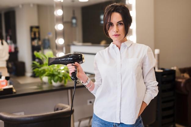 Cabeleireiro posando com secador de cabelo