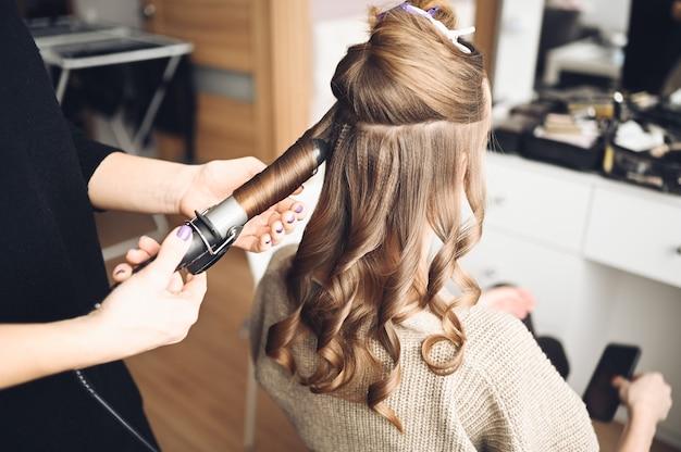 Cabeleireiro prepara mulher jovem e bonita para o evento, faz penteado cachos com um modelador de cachos para cliente no salão de beleza