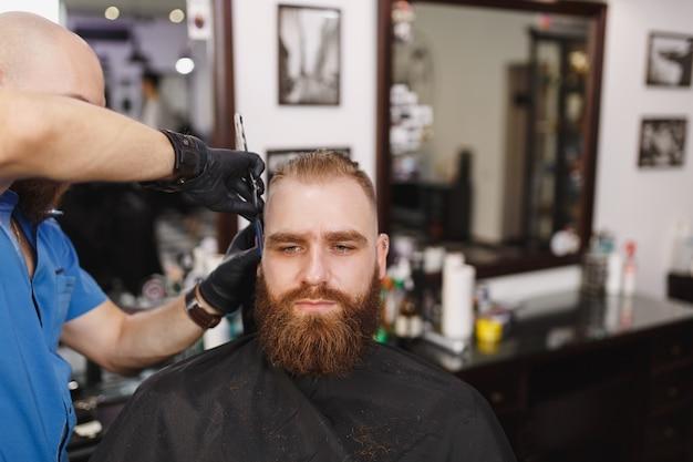 Cabeleireiro profissional atendendo cliente, barbeando uma barba espessa com navalha reta