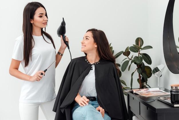 Cabeleireiro profissional com secagem na mão aconselha seu cliente qual o melhor penteado