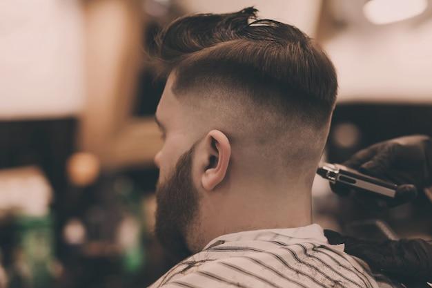 Cabeleireiro profissional corta o cabelo de um homem em um salão de beleza.