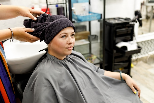Cabeleireiro profissional enxuga a cabeça do cliente com uma toalha