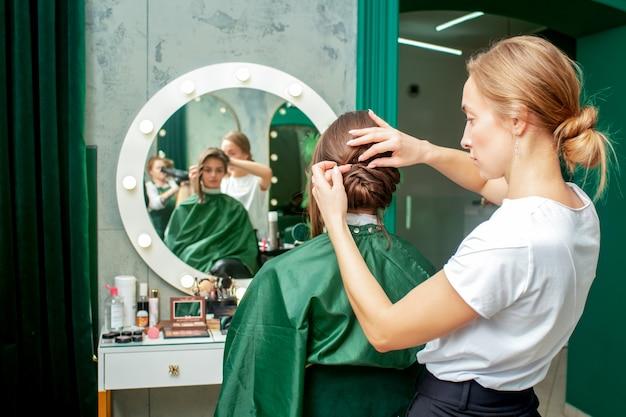 Cabeleireiro profissional faz o penteado da mulher no salão de beleza.