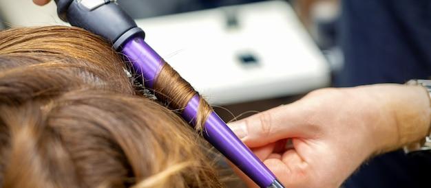 Cabeleireiro profissional faz penteado encaracolado ondulando para cabelos ruivos longos de jovem em salão de cabeleireiro