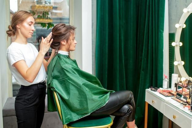 Cabeleireiro profissional faz penteado para mulher no salão de beleza.