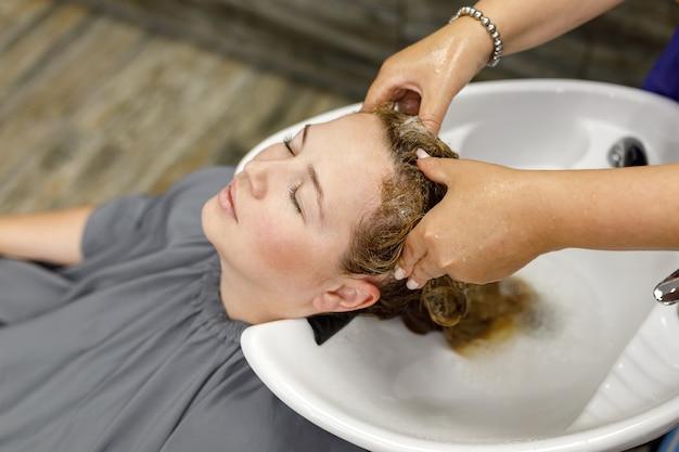 Cabeleireiro profissional irreconhecível lava o cabelo de sua cliente