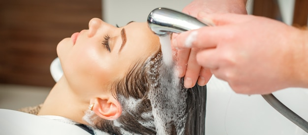Cabeleireiro profissional lavando cabelo de uma jovem