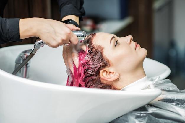 Cabeleireiro profissional, lavar o cabelo de um cliente bonito