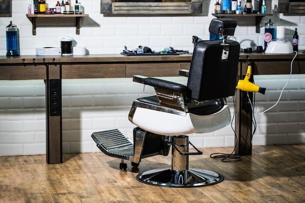 Cabeleireiro profissional no interior da barbearia. cadeira de barbearia.