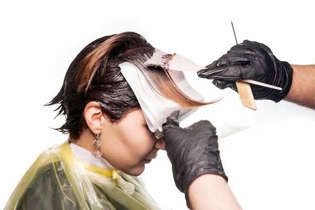 Cabeleireiro profissional tingindo o cabelo de seu cliente. tiro do estúdio. isolado no fundo branco.