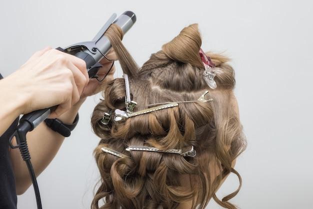 Cabeleireiro profissional torce o cabelo com um ferro de frisar no salão de beleza. crie a imagem da noiva loira. fechar-se.