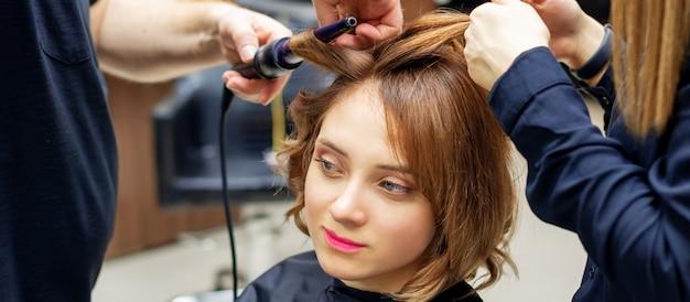 Cabeleireiro profissional torce os cachos de cabelo castanho claro comprido de mulher com modelador de cachos no salão de beleza. procedimentos de cabeleireiro