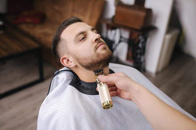 Cabeleireiro profissional usa um aparador de cabelo para franjar a barba de um homem bonito na barbearia. visão em primeira pessoa