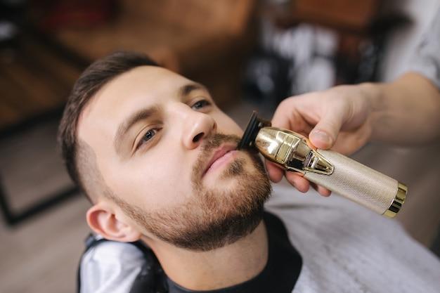 Cabeleireiro profissional usa um aparador de cabelo para franjar a barba de um homem bonito na barbearia.