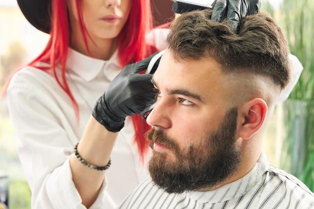 Cabeleireiro profissional usa um aparador de cabelo para franjar a barba de um homem bonito na barbearia