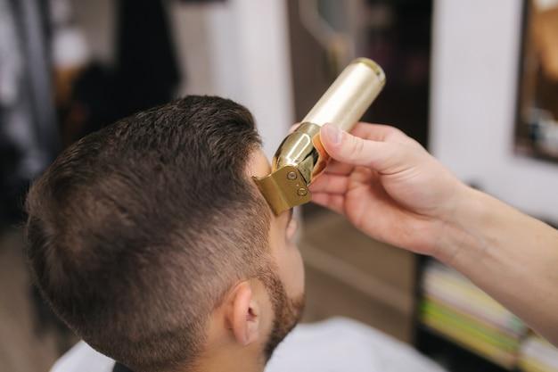 Cabeleireiro profissional usa um aparador de cabelo para franjar o cabelo de um homem bonito e barbudo. barbearia. fechar-se.