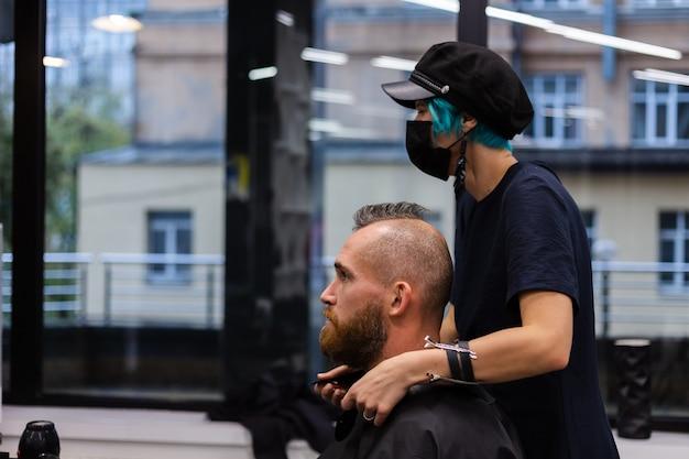 Cabeleireiro profissional usando máscara protetora, faz corte de cabelo para homem barbudo brutal em salão de beleza