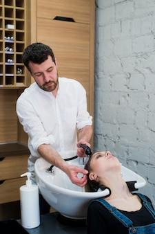 Cabeleireiro que lava o cabelo da menina adolescente no salão de beleza.