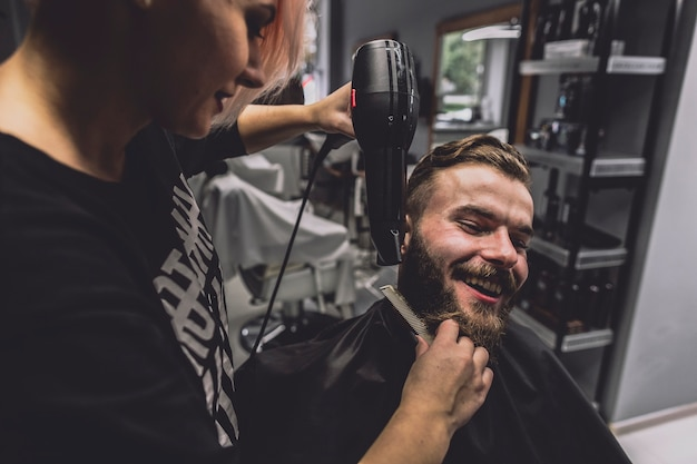 Cabeleireiro que seca a barba do homem bonito