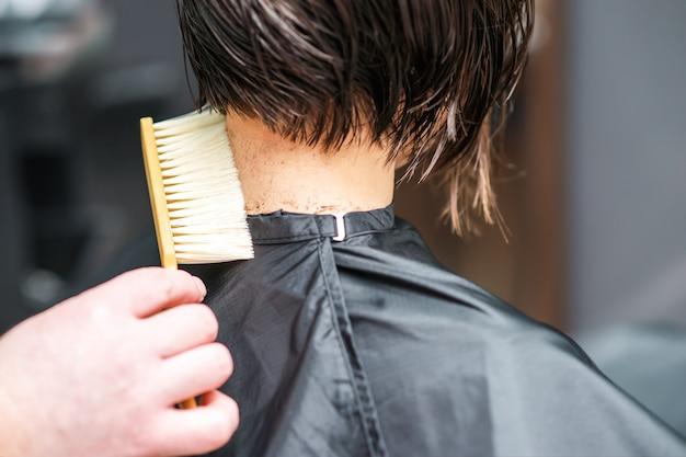 Cabeleireiro sacode o cabelo cortado do pescoço da mulher no salão de cabeleireiro.
