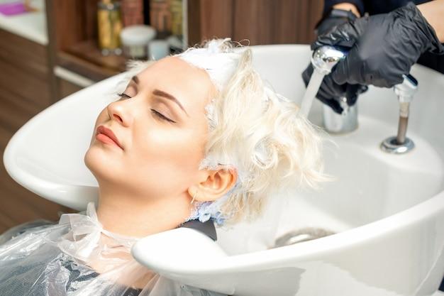Cabeleireiro se prepara para tirar a tinta branca do cabelo de uma jovem mulher branca na pia do salão de beleza