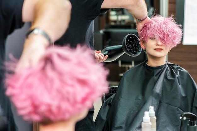 Cabeleireiro seca o cabelo com um secador de cabelo