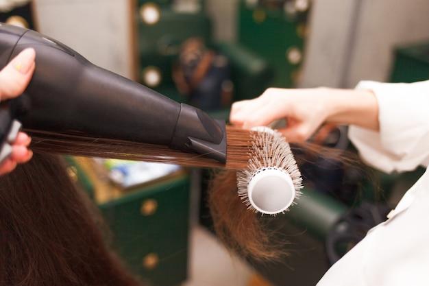 Cabeleireiro seca o cabelo de um cliente com secador de cabelo e pente. mulher no salão de beleza