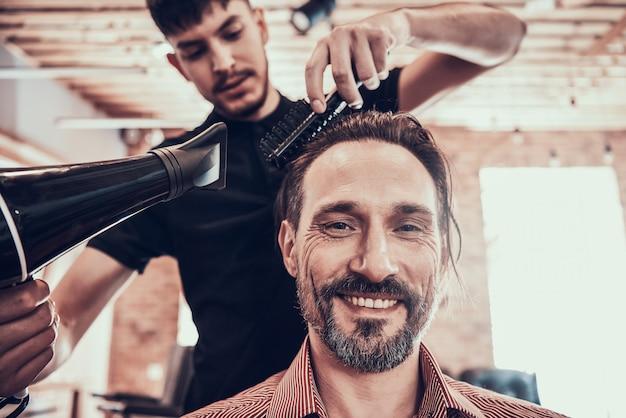 Cabeleireiro seca o cabelo para o cliente após o corte