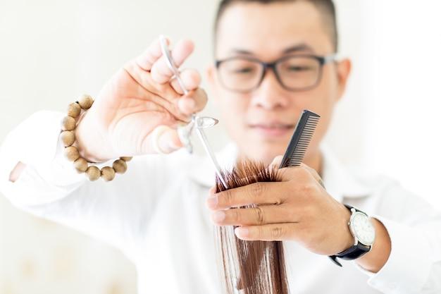 Cabeleireiro sério cortando cabelo com tesoura