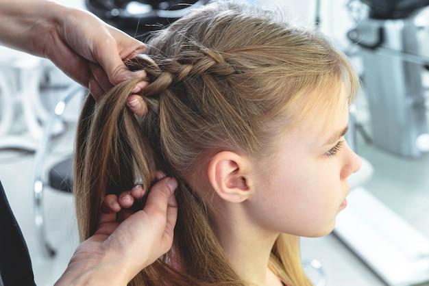 Cabeleireiro tece uma trança para uma menina loira pré-adolescente em um salão de beleza e cabelo