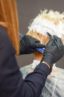 Cabeleireiro tinge o cabelo de uma jovem de cor branca em um salão de cabeleireiro.