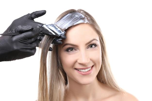 Cabeleireiro tingindo o cabelo de uma jovem mulher bonita em fundo branco