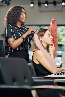 Cabeleireiro trabalhando com cliente em salão de beleza
