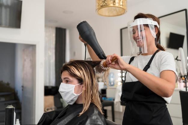 Cabeleireiro usando protetor facial e máscara de tecido do cliente