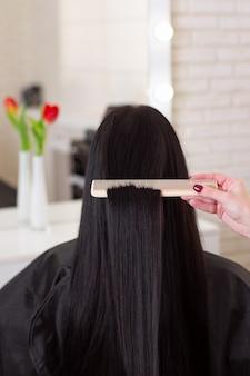 Cabeleireiros escovando cabelos longos e morenos em salão de beleza