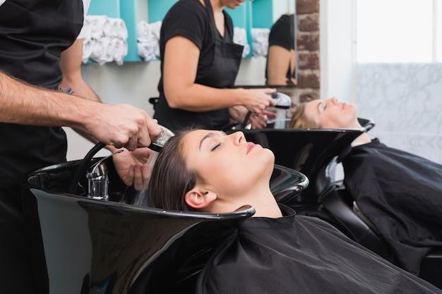 Cabeleireiros lavando os cabelos dos seus clientes