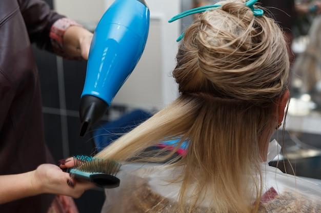 Cabeleireiros secando cabelos louros com secador e escova redonda