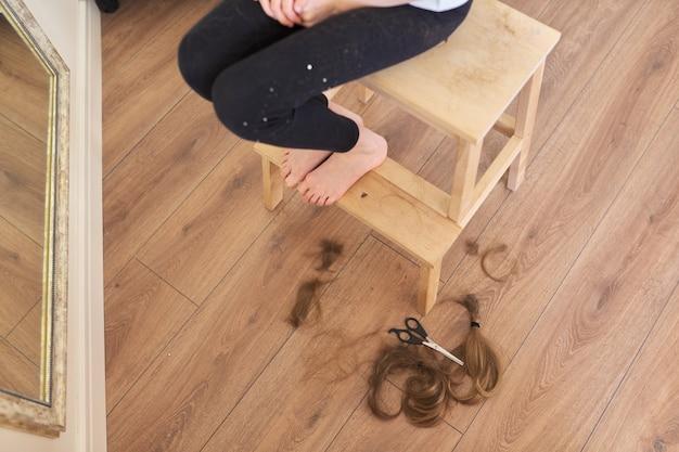 Cabelo aparado de menina criança e tesoura no chão, pés descalços de menina na cadeira em casa.