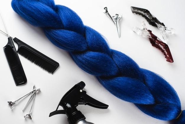 Cabelo azul kanekalon na superfície branca com pentes e acessórios de cabelo