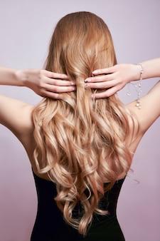 Cabelo bonito e forte de mulher, fortalecendo e restaurando as raízes do cabelo. linda manicure nas mãos de uma garota