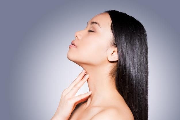 Cabelo brilhante e pele perfeita. vista lateral de uma bela jovem asiática sem camisa tocando seu pescoço e mantendo os olhos fechados em pé contra um fundo cinza