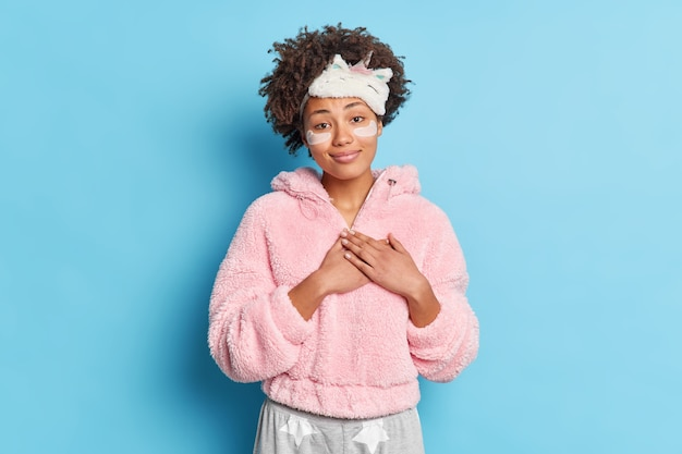 Cabelo cacheado fofo e sorridente mantém as mãos pressionadas contra o coração, faz gesto de gratidão e sente prazer ao ir para a cama vestido com pijamas e aplicar adesivos de colágeno para reduzir rugas em poses internas