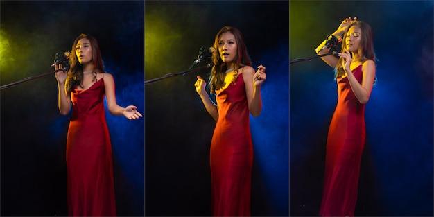 Cabelo castanho cacheado de mulher asiática usa vestido vermelho, canta uma música alto poder som sobre o condensador de microfone pendurado, compositor. absorvendo a fumaça do estúdio, copie o espaço