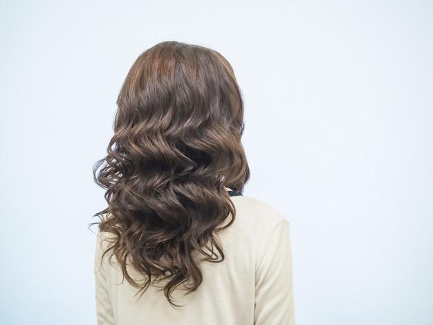 Cabelo castanho encaracolado. cachos castanhos de cabelo, penteados femininos.