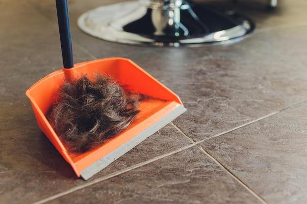 Cabelo castanho masculino com cabelos grisalhos. os bloqueios cortados estão no piso cerâmico claro.