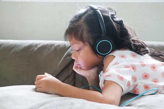 Cabelo comprido de criança asiática garota com fones de ouvido, ouvindo música e olhando o smartphone